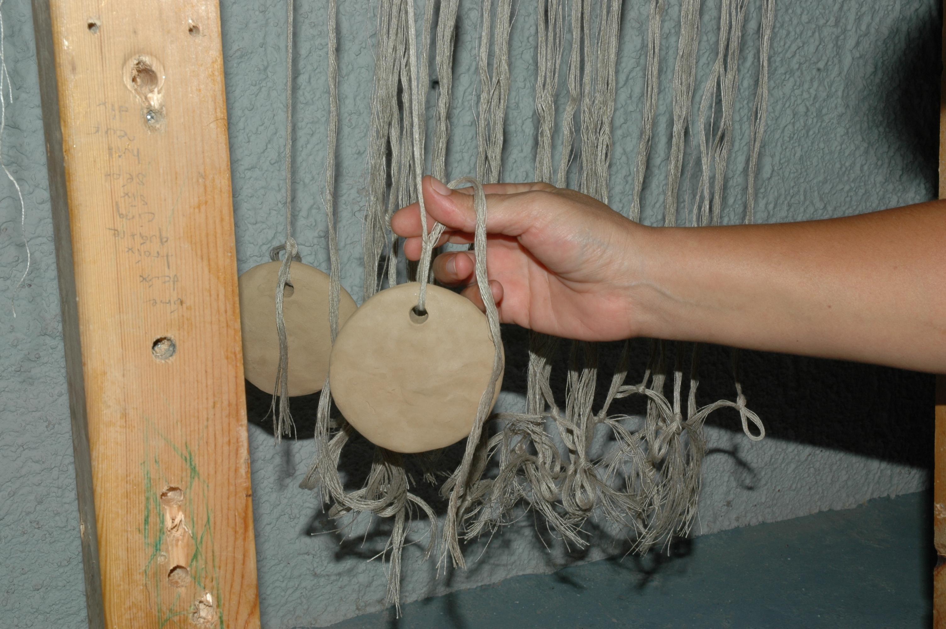 Attaching the warp threads to the loom-weights. Photo S. Spantidaki.